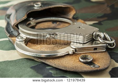 handcuffs on camouflage fabric background
