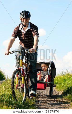 Papá conduce a sus dos hijos en una excursión de fin de semana con bicicletas en un día de verano en el hermoso paisaje