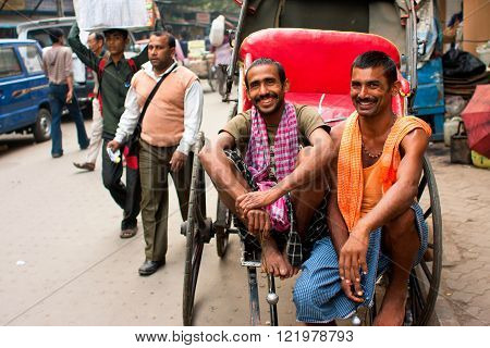 KOLKATA, INDIA - JAN 15: Two workers of hand-pulled rickshaw smile during the relax hour on the street on January 15, 2012. Kolkata's road space was only 6 perc. compared to 23 perc. in Delhi