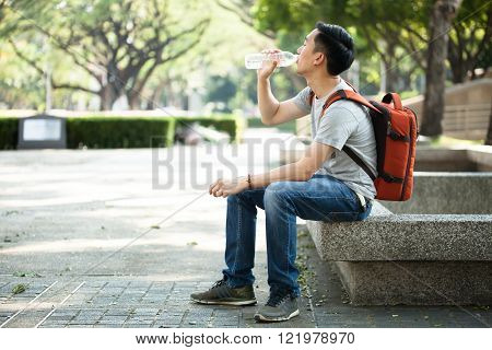 Man drinking water from bottle in the park - health care concept