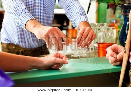 Barkeeper putting hard liquor glasses on bar, people waiting for a drink standing around (just hands)