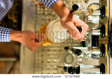 Man drawing a beer from tap on a kegerator in pub or inn