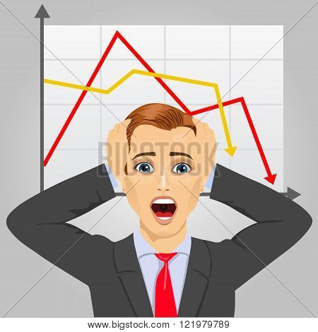 young businessman grabbing his head in economic crisis with line graph showing negative trend
