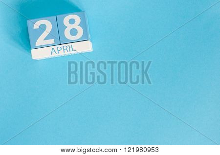 April 28th. Tax Day. Image of april 28 wooden color calendar on blue background.  Spring day, empty