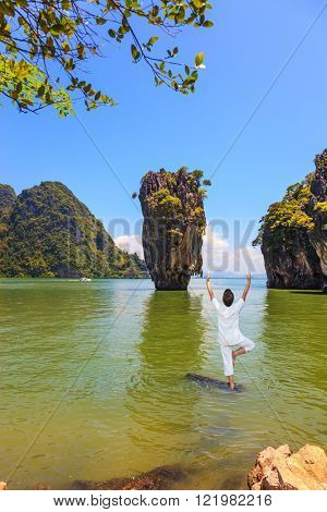 Exotic vacation in Thailand. Woman performs yoga pose standing in the water of the Andaman Sea