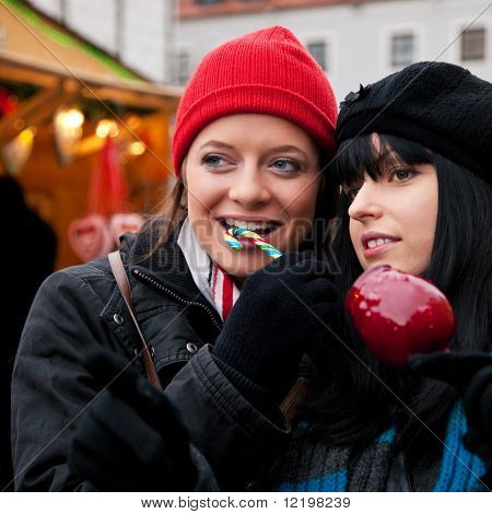 Two women on Christmas market eating apple and candy in front of a booth, it is cold