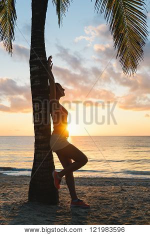 Fitness woman relaxing and resting after morning tropical beach workout at Riviera Maya Mexico. Travel and vacation relax.