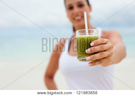 Fitness woman holding green healthy detox smoothie. Summer diet and nutrition for slim down concept.