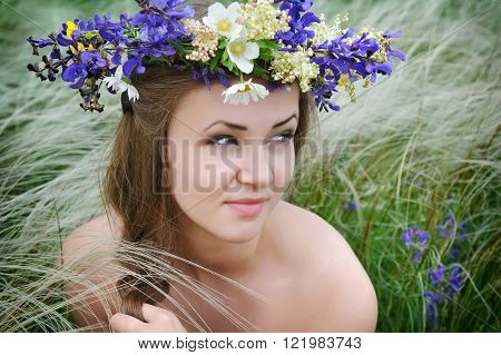 Beautiful Young Woman With Flower Wreath In The Grass Of Feather