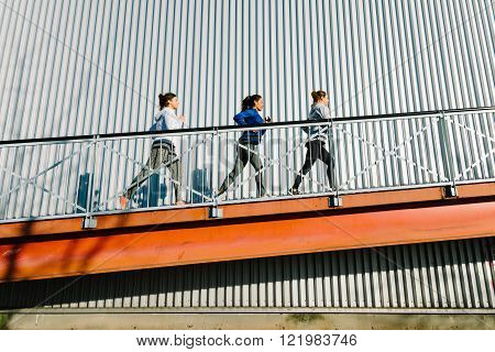Group of women running on a ramp. Urban outdoor training people.