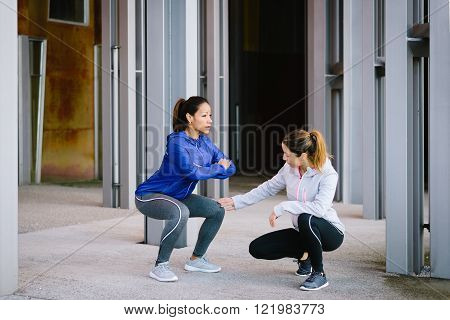 Two fitness women doing squat exercise workout outdoor. Female coach correcting knee position for legs exercising.