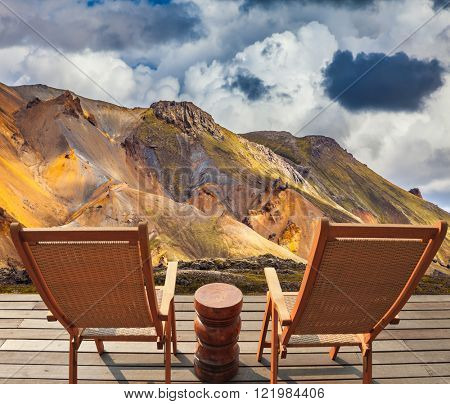 Two comfortable wooden chairs and small table stand for tired tourists.  The rhyolite mountains in volcanic summer tundra. Travel to Iceland in July