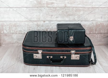 A stack of two old vintage black leather suitcase on a wooden background.