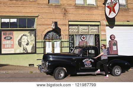 BISBEE, ARIZONA, FEBRUARY 25: The historic Lowell district on February 25, 2016, in Bisbee, Arizona. A model dressed 50s style poses by a refurbished 50s Texaco gas station in historic Lowell Arizona.