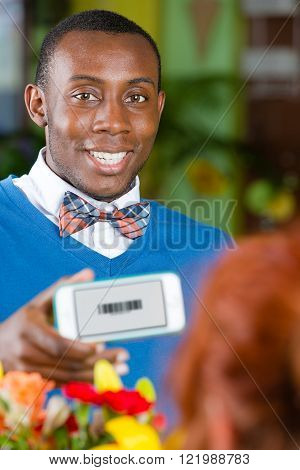 Customer in a busy flower shop holding smartphone with electronic coupon on the front