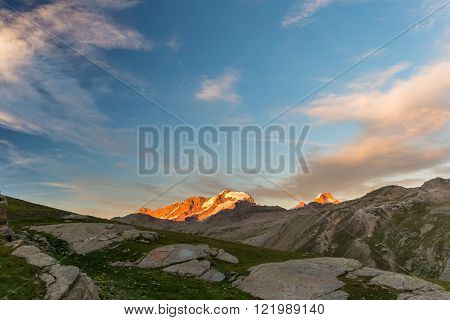 Sunset red light over the highest mountain peak in Piedmont (Italy) Gran Paradiso (4061 m) with his melting glaciers at the border with Valle d'Aosta and Vanoise National Park (France).