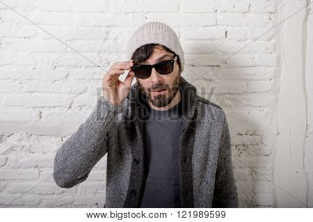 young attractive hipster and trendy style looking man posing cool with attitude dressing informal wearing casual beanie beard and sunglasses in male fashion concept