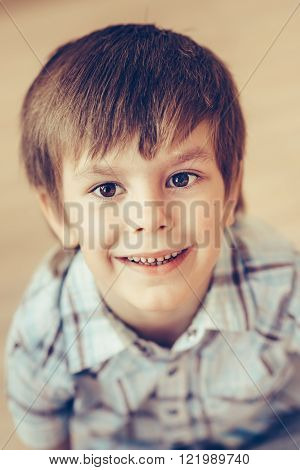 Closeup portrait of cute smiling little boy with brown eyes wearing checkered shirt sitting on floor and looking at camera. Happy childhood concept selective focus on eyes top view instagram filter
