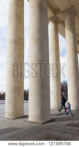 Moscow - March 13 2016: Central entrance to the Park of Culture and Rest named after Gorky a colonnade and the father and son come to the park March 13 2016 Moscow Russia