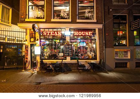 Amsterdam-May 01: Row of local steakhouses and restaurants at night in red-light district on May 012015 in Amsterdam the Netherlands.