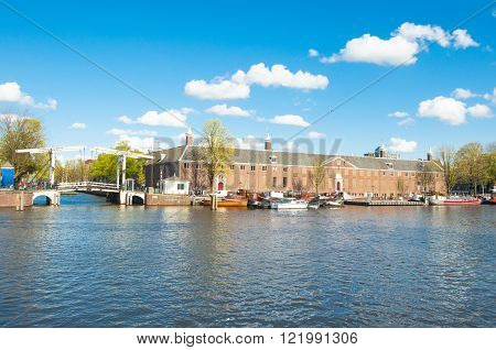 Amsterdam-April 30: Amsterdam cityscape Magere Brug also known as Skinny Bridge and Hermitage Amsterdam are visible in the distance on April 30 2015 the Netherlands.