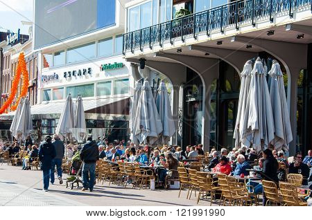 Amsterdam-April 30: Undefined people have drinks in outdoor cafe with Rembrandtplein view famous Escape club is visible in the background on April 30 2015 the Netherlands.