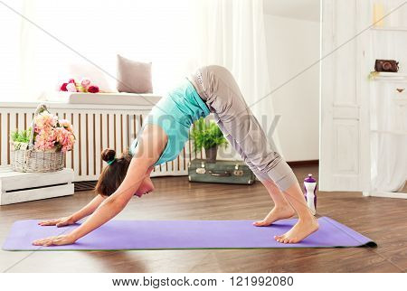 young beautiful girl engaged in yoga. meditation yoga studio in the daytime. Girl in a downward dog pose. Purple yoga mat and water bottle. Yoga at home.