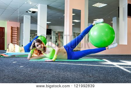 athletic girl and healthy lifestyle concept exercising with fitness ball on a mat in the gym..