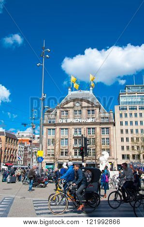 AMSTERDAM-APRIL 30: Undefined people cross the street on bikes on Dam Square De Bijenkorf flagship store is visible on the background on April 30 2015 in Amsterdam Netherlands.