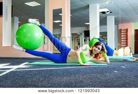 athletic girl and healthy lifestyle concept exercising with fitness ball on a mat in the gym