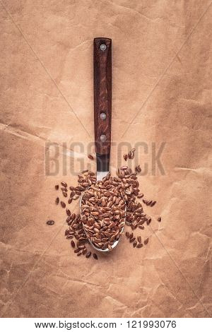 Healthy food. Flax seeds linseed on kitchen spoon old paper background