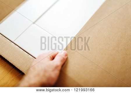 Man installing new white furniture after relocation - opening cardboard box