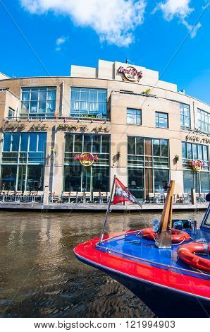 AMSTERDAM-APRIL 30: Hard Rock Cafe on the Singelgrachtkering Canal with boat on April 302015. Hard Rock Cafe Amsterdam offers an immersive experience in the waterside restaurant and cocktail bar.
