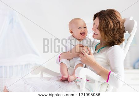 Young mother holding her newborn child. Mom nursing baby. Woman and new born boy in white bedroom with rocking chair and blue crib. Nursery interior. Mother playing with laughing kid. Family at home