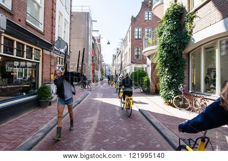 AMSTERDAM-APRIL 30: Jordaan neighbourhood tourists ride bicycles on April 30, 2015. The Jordaan is a neighbourhood of the city of Amsterdam with its famous art galleries particularly for modern art.