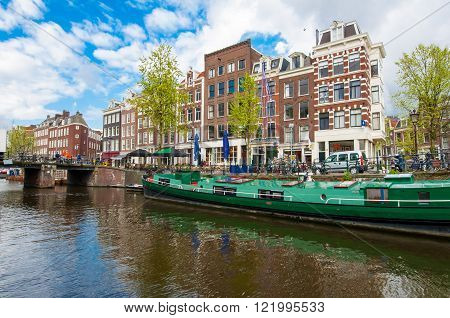 Amsterdam canal with a houseboat along the bank Netherlands.