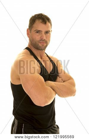 A man in his fitness tank with his arms folded .