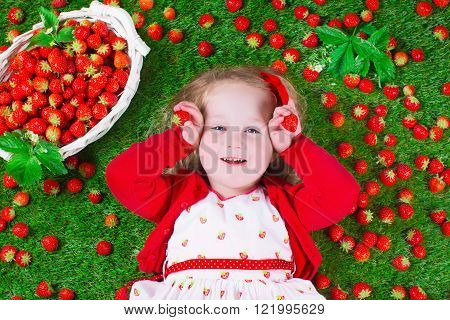 Child eating strawberry. Little girl playing peek a boo holding fresh ripe strawberries. Kids eating fruit relaxing on a lawn. Children summer fun on a farm picking berry.