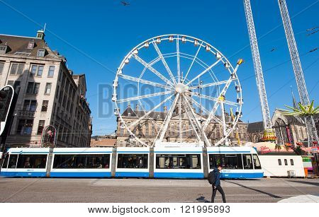 AMSTERDAM-APRIL 27, 2015: Big wheel on Dam Square on the eve of King's Day Madam Tussaud's museum on the left-hand side on April 27 2015. King's Day is the largest open-air festivity in Amsterdam.