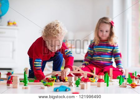 Children playing with wooden train. Toddler kid and baby play with blocks trains and cars. Educational toys for preschool and kindergarten child. Boy and girl build toy railroad at home or daycare.