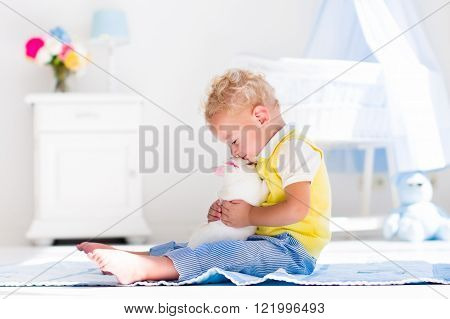 Cute blond curly baby boy playing with rabbit in a white sunny bedroom. Kids and pets at home. Children and animals play indoors. Funny toddler kid holding Easter bunny. Child taking care of an animal