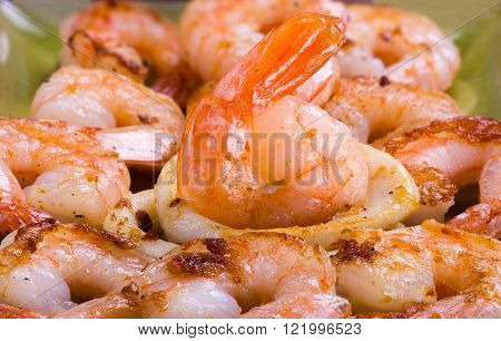 Fried shrimps and rings of a squid on a grill