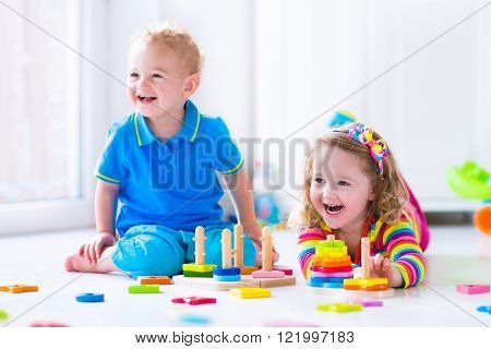 Kids playing with wooden toys. Two children cute toddler girl and funny baby boy playing with toy blocks building towers at home or day care. Educational child toys for preschool and kindergarten.