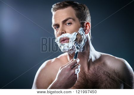 Studio portrait of handsome young man. Man with naked torso and shaving foam on face looking at camera and shaving