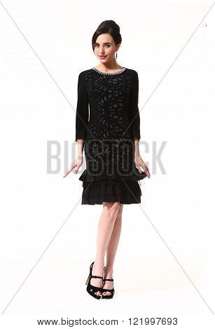 indian  business executive woman with updo hair style in formal black cocktail party sleeveless dress long sleeve dress high heel shoes standing full