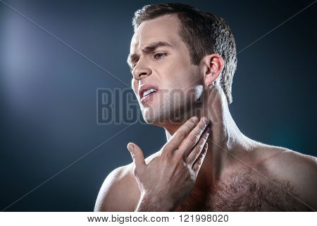 Studio portrait of handsome young man. Man with naked torso having skin irritation after shaving