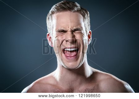 Studio portrait of handsome young man. Clean shaven man with naked torso looking at camera and screaming