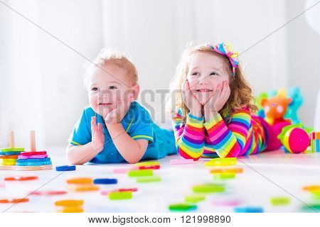 Preschooler child playing with colorful toy blocks. Kids play with educational wooden toys at kindergarten or day care. Preschool children build tower with wood block. Toddler kid in nursery.