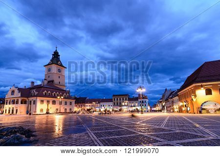 Brasov, Romania - February 23: The Council Square on February 23, 2016 in Brasov, Romania. Panoramic vertical view with famous buildings, beautiful sky in evening wintertime and public lights.