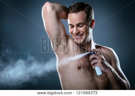 Studio portrait of handsome young man. Clean shaven man with naked torso using deodorant and smiling